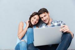 Portrait de jeunes couples heureux utilisant l'ordinateur portable au-dessus du fond gris Photographie stock libre de droits
