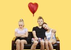 Portrait de jeunes couples se reposant sur le sofa avec l'ami féminin se sentant gauche au-dessus du fond jaune Photographie stock