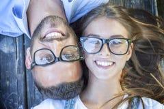 Portrait de jeunes couples se trouvant sur le banc en bois Photos stock