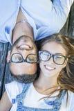 Portrait de jeunes couples se trouvant sur le banc en bois Images stock
