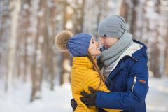 Portrait de jeunes couples semblant face à face dans une forêt pendant l'hiver Image libre de droits