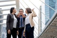 Portrait de jeunes femmes asiatiques agressives dans le combat de tenue de soirée ou de femme d'affaires tandis que l'homme dissu image libre de droits