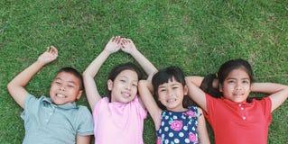Portrait de jeunes filles asiatiques de garçon ayant le bon temps dans le parc Photos stock