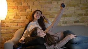 Portrait de jeunes filles caucasiennes détendant sur le sofa et faisant des selfie-photos utilisant le smartphone en atmosphère à clips vidéos