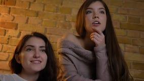 Portrait de jeunes filles caucasiennes s'asseyant ensemble et de film de observation avec le grand intérêt pour l'atmosphère à la banque de vidéos