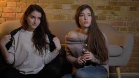 Portrait de jeunes filles caucasiennes s'asseyant sur le vin potable de plancher et le film de observation attentivement en atmos banque de vidéos