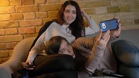 Portrait de jeunes filles caucasiennes se trouvant sur le sofa et faisant des selfie-photos utilisant le smartphone en atmosphère banque de vidéos