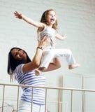 Portrait de jeunes mère et fille de sourire à la maison, famille heureuse ayant ensemble l'amusement, concept de personnes de mod Image libre de droits