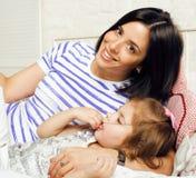 Portrait de jeunes mère et fille de sourire à la maison, famille heureuse ayant ensemble l'amusement, concept de personnes de mod Photo stock