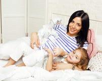 Portrait de jeunes mère et fille de sourire à la maison, famille heureuse ayant ensemble l'amusement, concept de personnes de mod Photographie stock libre de droits