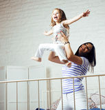 Portrait de jeunes mère et fille de sourire à la maison, famille heureuse ayant ensemble l'amusement, concept de personnes de mod Photos stock