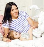 Portrait de jeunes mère et fille de sourire à la maison, famille heureuse ayant ensemble l'amusement, concept de personnes de mod Image stock