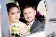 Portrait de jeunes nouveaux mariés affectueux d'un couple à côté d'un bouquet dans la fenêtre d'une voiture de mariage Photos stock