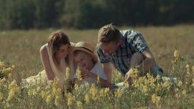 Portrait de jeunes parents donnant à leur enfant des baisers sur des joues clips vidéos