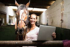 Portrait de jockey féminin tenant l'ordinateur portable tout en se tenant prêt le cheval images libres de droits