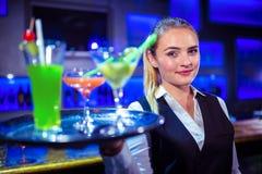 Portrait de joli barman tenant le plateau de portion avec des cocktails image stock