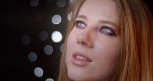 Portrait de joli modèle blond avec le maquillage lumineux observant être vers le haut rêveur et mystérieux sur le fond de bokeh banque de vidéos