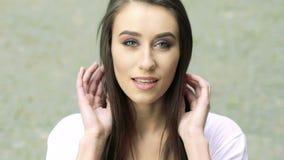 Portrait de jolie brune regardant sur l'appareil-photo et le sourire lentement banque de vidéos