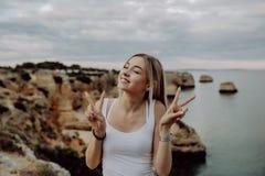 Portrait de jolie femme avec le geste de victoire posant sur des sourires de plage rocheuse à la caméra photographie stock