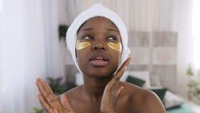 Portrait de jolie jeune femme africaine avec les corrections d'or médicales sous des yeux tout en se tenant dans la chambre à cou banque de vidéos