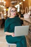 Portrait de jolie jeune femme d'affaires en verres se reposant sur le lieu de travail photographie stock libre de droits