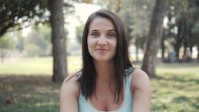 Portrait de jolie jeune femme se reposant sur la pelouse en parc en Sunny Summer Day clips vidéos