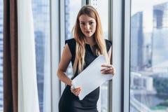 Portrait de jolie jeune femme tenant des documents regardant l'appareil-photo se tenant dans le bureau Photos stock