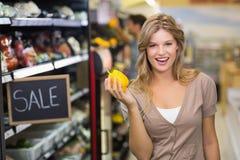 Portrait de jolis légumes de achat de sourire d'une femme blonde Photos stock
