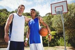 Portrait de joueur de basket avec le bras autour Images stock