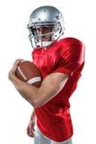 Portrait de joueur de football américain sûr dans le débardeur rouge tenant la boule photos libres de droits