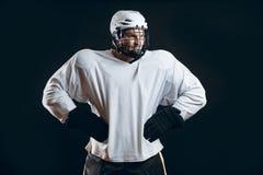 Portrait de joueur de glace-hockey avec le bâton de hockey photographie stock