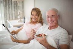 Portrait de journal de sourire de lecture de couples tout en prenant le petit déjeuner Image stock
