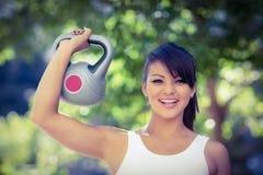 Portrait de kettlebell de levage de sourire de femme sportive Images libres de droits