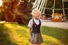 Portrait de l'écolière dans l'uniforme riant et se réjouissant en été en parc photo stock