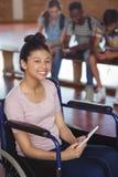 Portrait de l'écolière handicapée à l'aide du comprimé numérique avec des camarades de classe à l'arrière-plan Photo stock