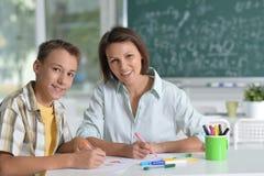 Portrait de l'écolier et du professeur s'asseyant à la salle de classe image libre de droits