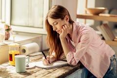Portrait de l'écriture de jeune fille dans le carnet, se tenant dans la cuisine Images libres de droits