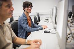 Portrait de l'étudiant heureux à l'aide de l'ordinateur Photo stock