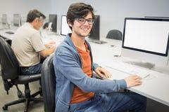 Portrait de l'étudiant heureux à l'aide de l'ordinateur Image libre de droits