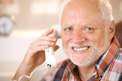 Portrait de l'aîné de sourire à l'aide du téléphone de ligne terrestre Images stock