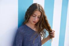 Portrait de l'adolescence de fille de brune dans le mur de rayures bleues photos libres de droits