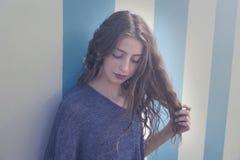 Portrait de l'adolescence de fille de brune dans le mur de rayures bleues photo stock