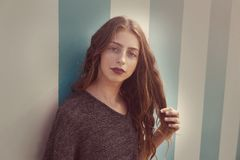 Portrait de l'adolescence de fille de brune dans le mur de rayures bleues photographie stock libre de droits