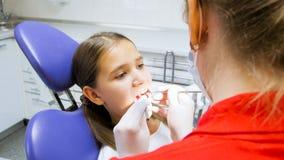 Portrait de l'adolescente faisant examiner ses dents par le dentiste images stock