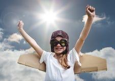 Portrait de l'enfant de sourire enthousiaste feignant pour être un pilote sur le fond lumineux de lumière du soleil Photographie stock libre de droits
