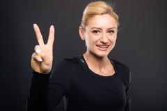 Portrait de l'entraîneur féminin de joli gymnase montrant le geste de paix Image libre de droits