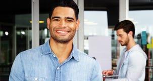 Portrait de l'exécutif masculin à l'aide du téléphone portable avec son collègue à l'arrière-plan banque de vidéos