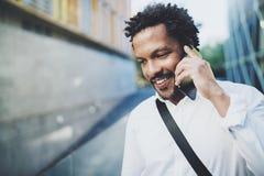 Portrait de l'homme africain américain heureux à l'aide du smartphone pour appeler des amis à la rue ensoleillée Concept des jeun Photographie stock libre de droits