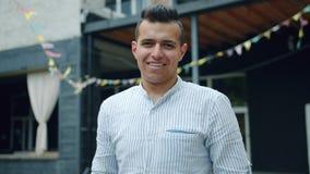 Portrait de l'homme arabe joyeux se tenant dehors avec le visage heureux regardant la caméra clips vidéos