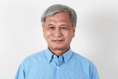 Portrait de l'homme asiatique supérieur attirant souriant et regardant l'appareil-photo dans le studio photo libre de droits